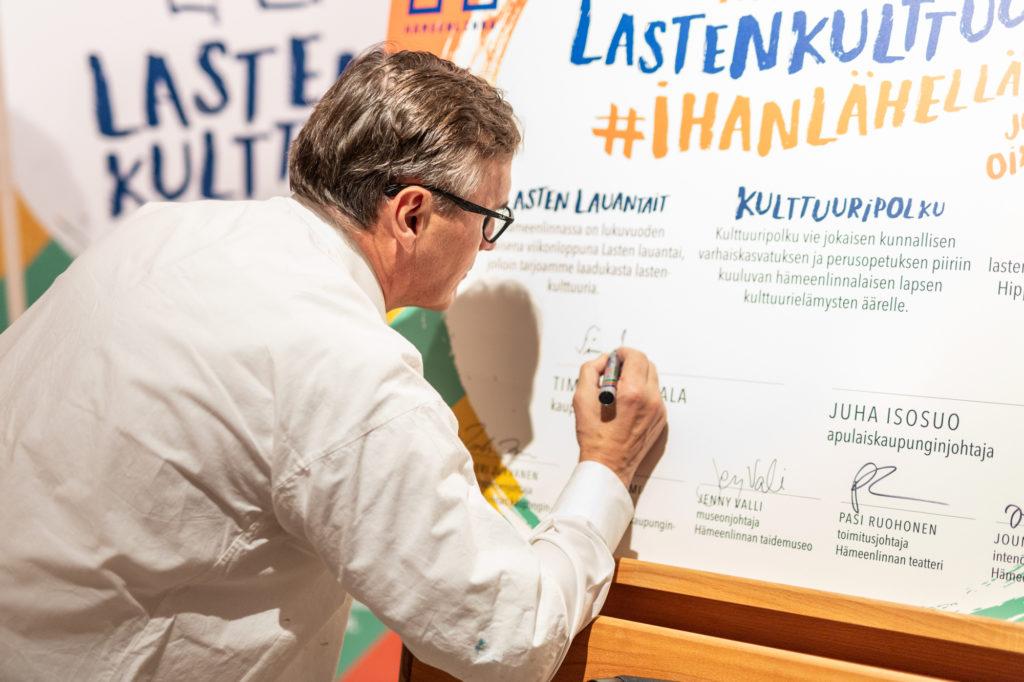 Kaupungijohtaja Timo Kenakkala allekirjoittamassa Hämeenlinnan lastenkulttuurilupausta.