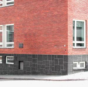Punatiilisen asuinrakennuksen kulmaus, jossa muistolaatta on.