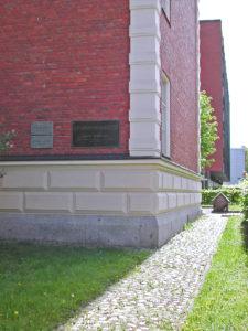 Punainen tiilirakennus, jonka seinässä on muistolaatta.