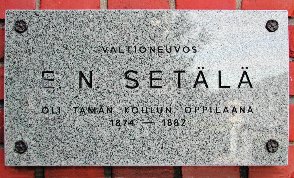 Lähikuva muistolaatasta, jossa teksti: Valtioneuvos E.N. Setälä oli tämän koulun oppilas